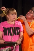 Chantelle in bright pink top has her neck measured for a noose by John Stern the Witchfinder's right hand man in bright orange