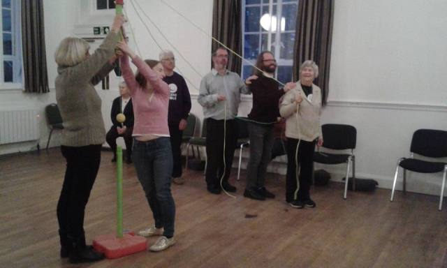 Denise, Wayne, Andy and Dave explore staging possibilities. Each stands behind the other in a line holding a rope attached to a central post, like a maypole, which Jenni and Steph are holding.