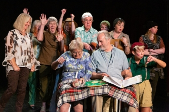 Ellen and George sit with a scrabble board on their knee. The villagers gather behind them